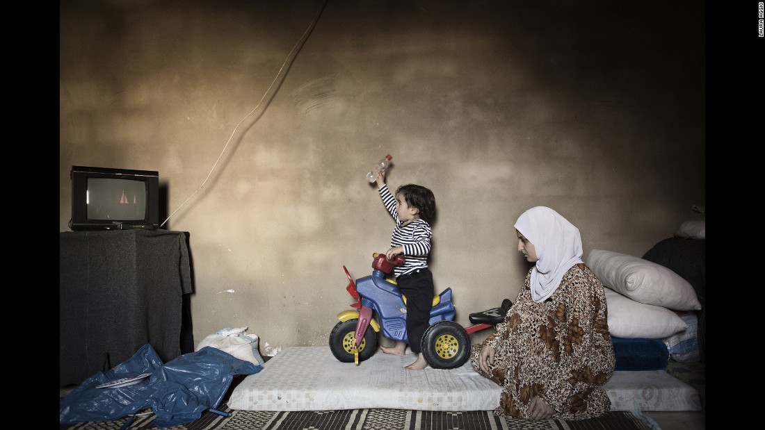 Marwa, 15, watches her son play on a tricycle. She married three years ago and left Syria a year after that.