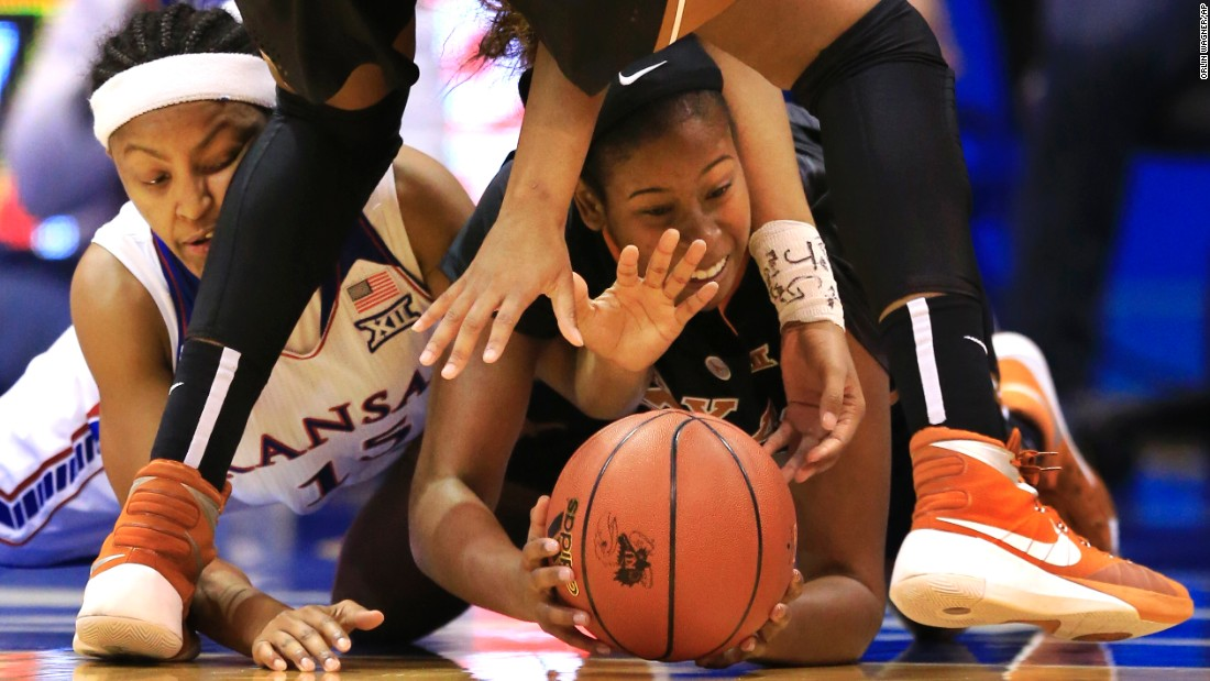 Kansas' Aisia Robertson, left, and Texas' Ariel Atkins dive for a loose ball during a game in Lawrence, Kansas, on Wednesday, January 13.