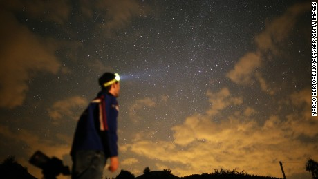 A photographer prepares to take pictures of a meteor shower in the village of Crissolo, near Cuneo, in the Monviso Alps region of northern Italy.