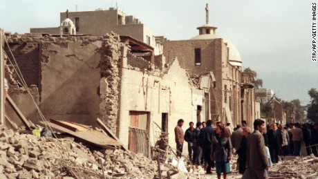 A photo taken on February 16, 1991 shows Iraqi civil defence workers and civilians looking at the damage near a Christian church caused by an allied bombing raid in Baghdad.