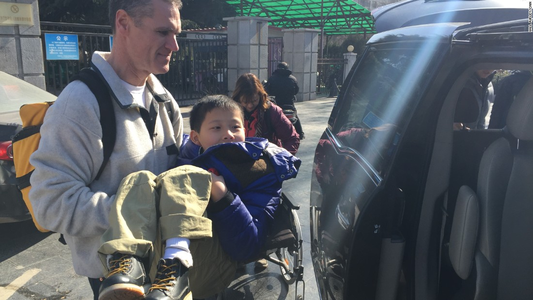Brian Wilson carries JiaJia to a waiting van. The little boy suffers from spina bifida. Botched surgery left him paralyzed from the waist down. The Wilsons hope further surgeries can help correct some of his problems.