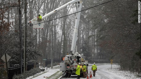 Duke Energy employees work to restore power in a neighborhood in Matthews, N.C., Friday, Jan. 22, 2016. A massive blizzard began dumping snow on the southern and eastern United States on Friday, with mass flight cancellations, five states declaring states of emergency and more than 2 feet (60 centimeters) predicted for Washington alone. (AP Photo/Chuck Burton)