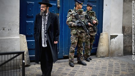 Armed soldiers patrol outside a School in the Jewish quarter of the Marais district on January 13, 2015 in Paris.