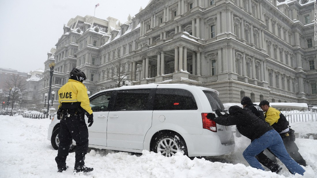 Secret Service officers push a police car stuck in front of the Eisenhower Executive Office Building in Washington on January 23.