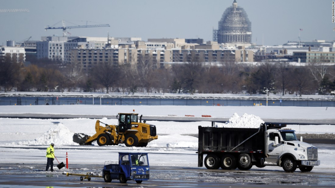 Workers remove snow on the tarmac at  Ronald Reagan National Airport on January 24.