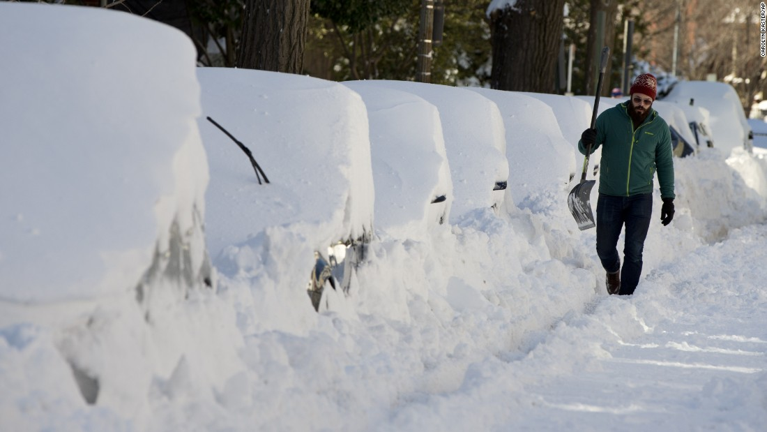 A man walks with a shovel past a line of snowed-in cars in Washington on January 24.