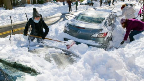 Rhianna McCarte, 30,  joins her neighbors to dig out their cars in Alexandria, Va., Sunday, Jan. 24, 2016. Millions of Americans were preparing to dig themselves out Sunday after a mammoth blizzard with hurricane-force winds and record-setting snowfall brought much of the East Coast to an icy standstill. (AP Photo/Cliff Owen)