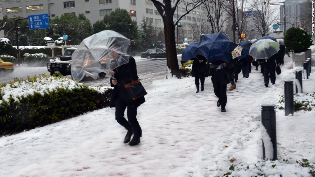 Commuters walk on a snow covered road in Tokyo on January 18 where heavy snow blanketed the metropolitan area and transportation systems were paralyzed. Many cities throughout western and northern Japan have seen record snow falls, while the usually-warm Okinawa island saw snowfall for the first time ever since record-keeping began in 1966.