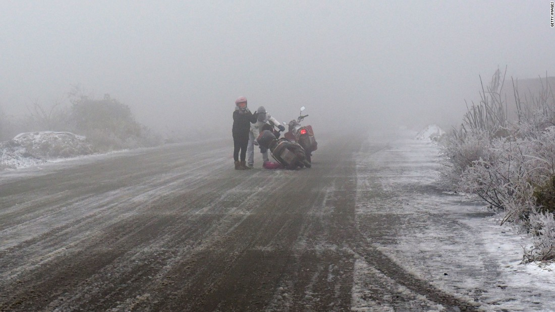 A motorbike rider falls down on an ice-covered highway in Shaoguan, in China's Guangdong province on January 23.