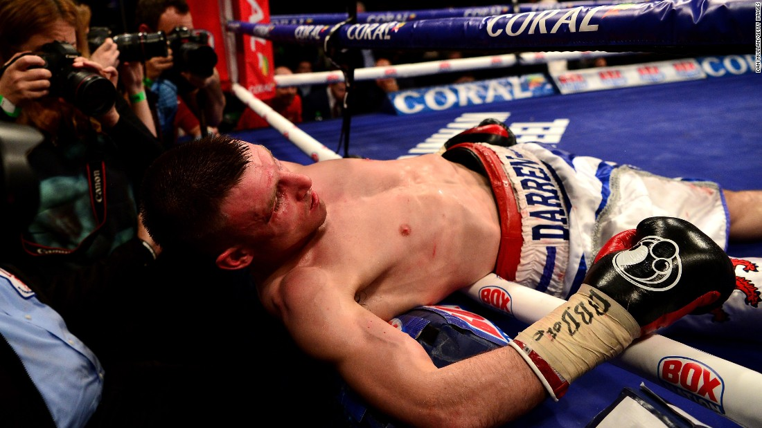 Ringside journalists photograph Darren Traynor after he was knocked through the ropes by Ryan Walsh during a featherweight bout in London on Friday, January 22. Walsh stopped Traynor in the fifth round.