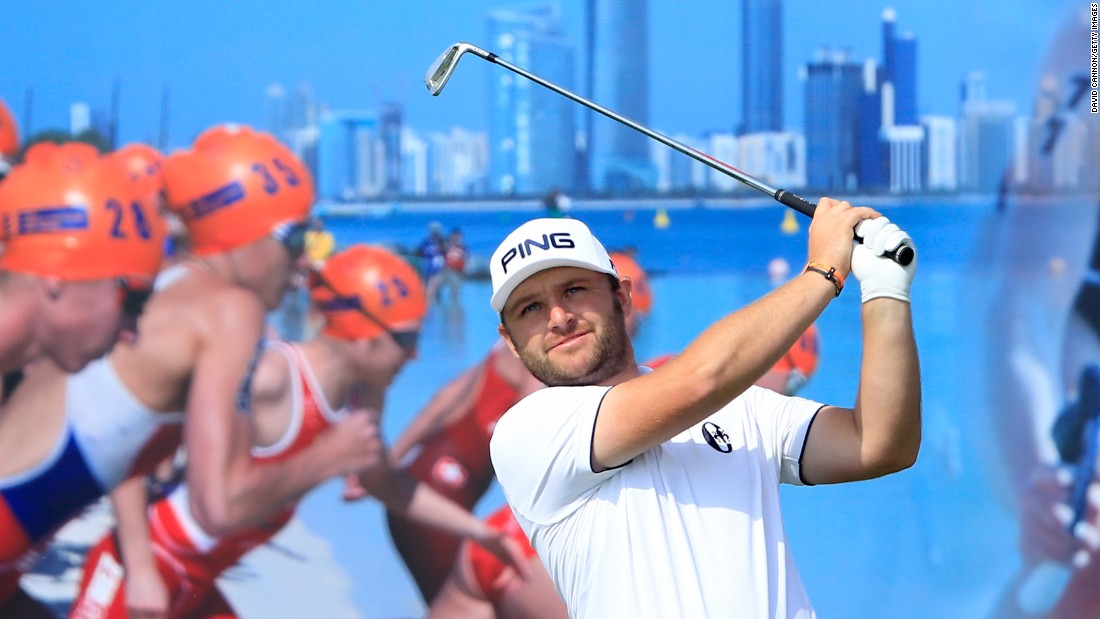 A triathlon advertisement is the backdrop for golfer Andy Sullivan as he plays a shot at the Abu Dhabi Championship on Friday, January 22.