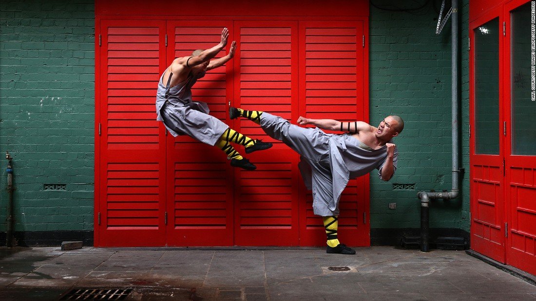 "Shaolin monks pose for a photo in London's Chinatown. Drewell attempts to emulate their athleticism in his routine but admits it's hard. ""I try to do a kind of high kick while they are fighting,"" he says. ""I tried to do it on the horse but my feet don't go so high -- but I try!""<br />"