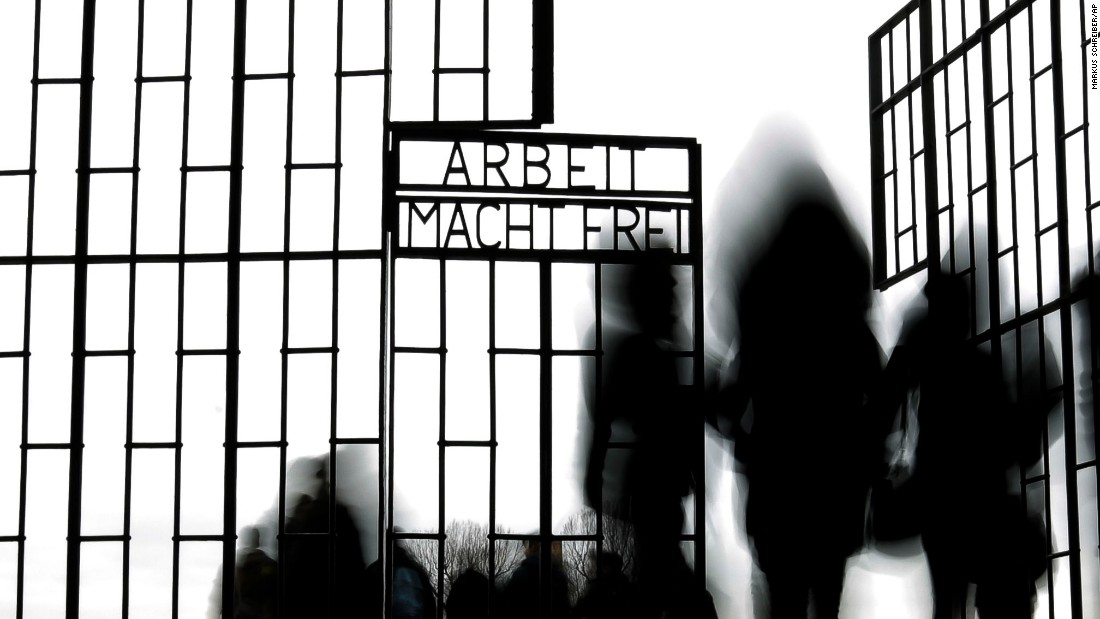 "People in Oranienburg, Germany, walk through the gate of the Sachsenhausen concentration camp on Wednesday, January 27. It was International Holocaust Remembrance Day. The phrase on the gate translates to ""Work sets you free."""