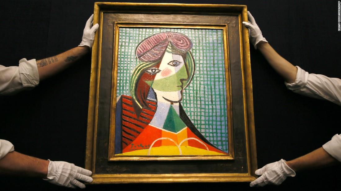 "Sotheby's employees adjust the Pablo Picasso painting ""Tete de Femme"" at an auction room in London on Thursday, January 28. The painting is estimated to be worth $23 million-$29 million. It goes up for auction on February 3."