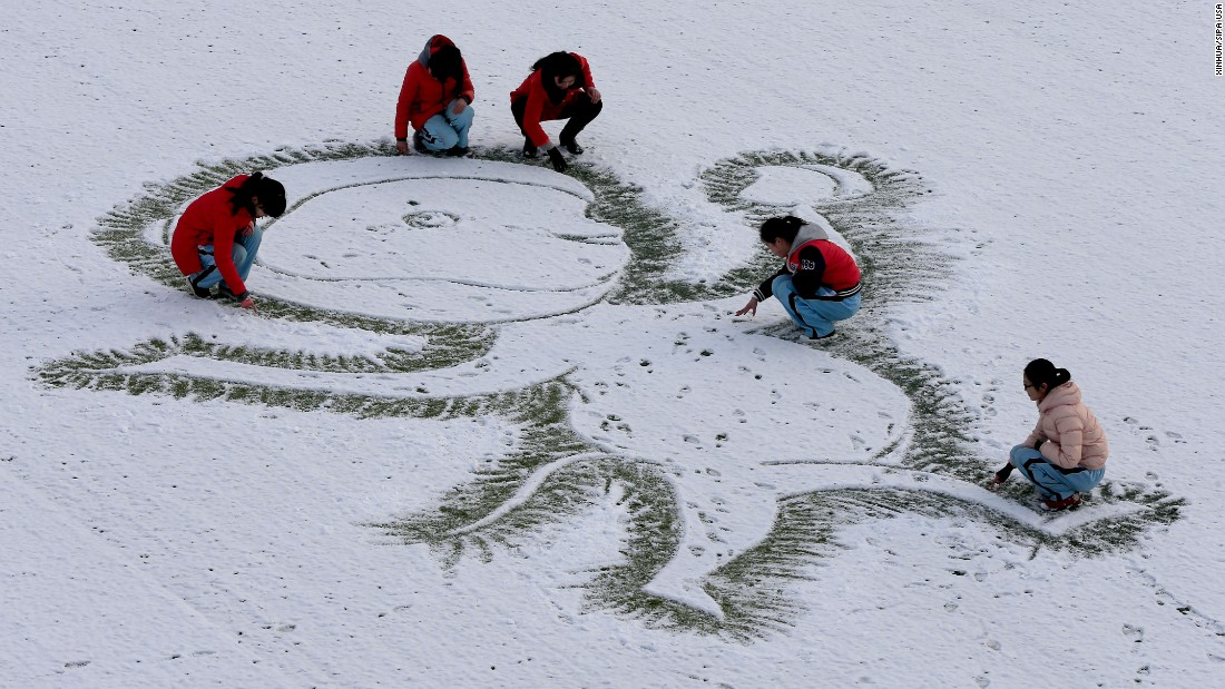 A teacher and students draw a monkey on the snow-covered ground in China's Jiangsu Province on Thursday, January 21.
