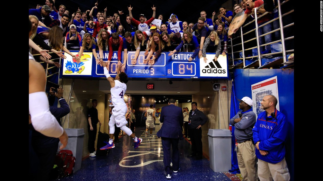 Devonte' Graham high-fives Kansas fans after the Jayhawks defeated Kentucky in Lawrence, Kansas, on Saturday, January 30. Kansas won 90-84 in overtime.