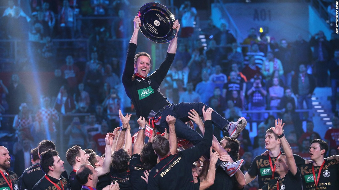 Germany head coach Dagur Sigurdsson is lifted by his players Sunday, January 31, after they won the European Handball Championship in Krakow, Poland. The Germans defeated Spain in the final to win their first European title since 2004.