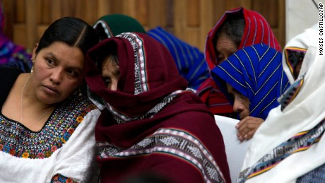 Women cover their faces while listening to an interpreter, left, in the ex-military officers' trial in Guatemala.
