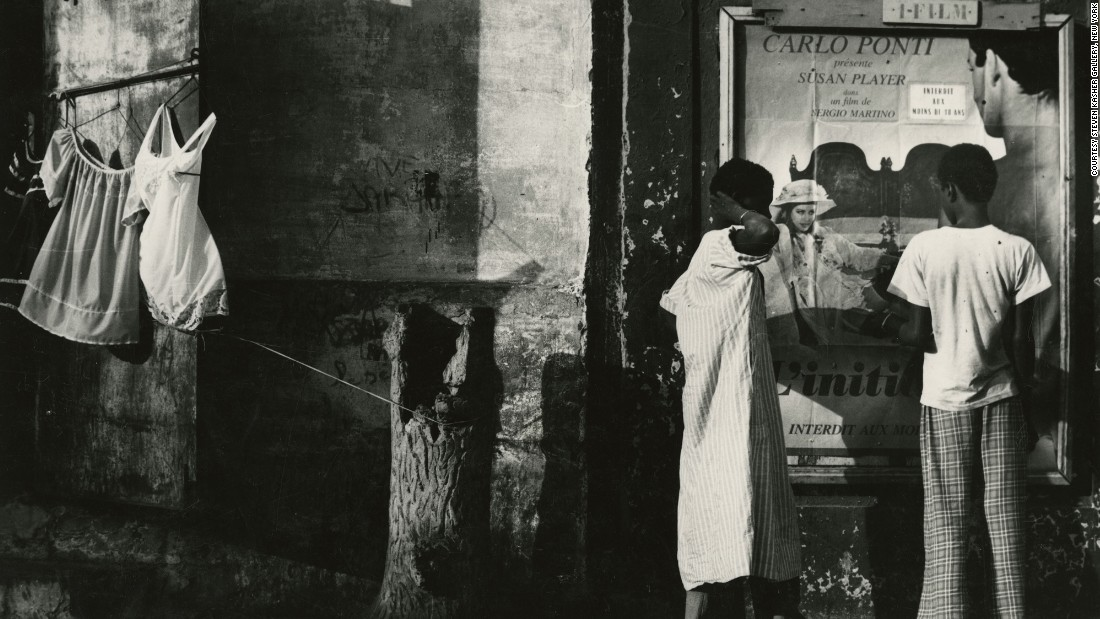 Draper occasionally left New York to photograph the world. This photo, taken in 1978 in Dakar, Senegal, shows a man and a woman next to a poster for an Italian B movie.