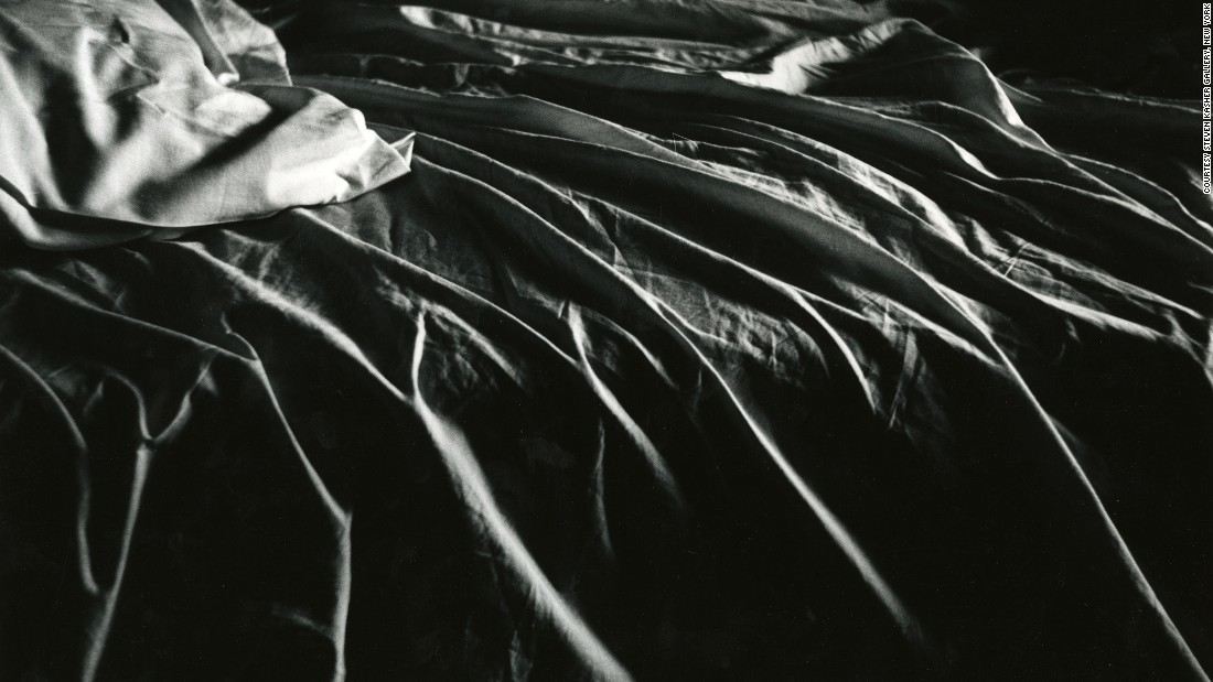 This 1958 image shows the interplay of light and shadow on the linens of an unmade bed.