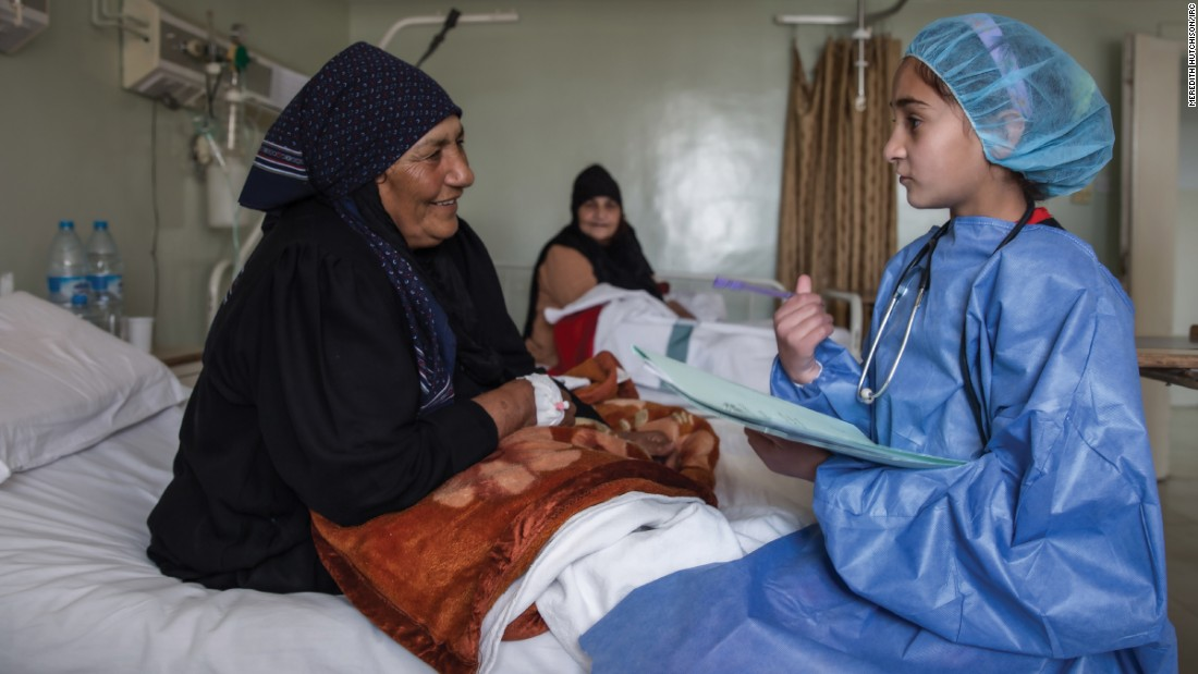 """In this image, I am in the future and a well-respected physician at a major hospital in Syria. I am asking a patient about her pain and helping her to get better. My mother was born and raised in a village and didn't go to school, but as a young girl, I had the opportunity to learn and grow into a great doctor."""