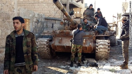 Syrian government forces chat by a tank near the Shiite villages of Nubul and Zahraa.