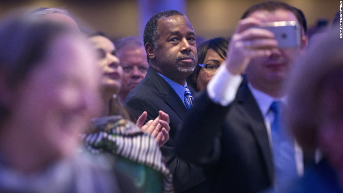 Republican presidential candidate Ben Carson and his wife Candy Carson stand up to applaud the arrival of President Barack Obama and first lady Michelle Obama at the National Prayer Breakfast in Washington on Thursday, February 4.