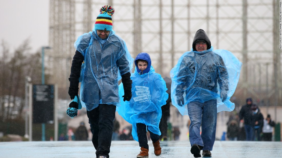 Manchester City supporters make their way to the stadium in wet weather prior to the Premier League match between Manchester City and Leicester City at the Etihad Stadium on February 6, 2016 in Manchester, England.