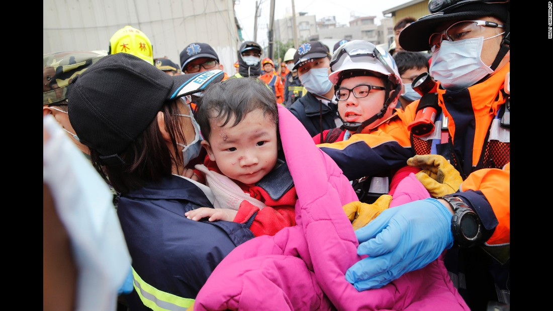 A boy is rescued from a collapsed building in Tainan on February 6. More than 200 people were rescued from damaged structures, many from a 16-story residential building that collapsed in Tainan, officials told CNN.