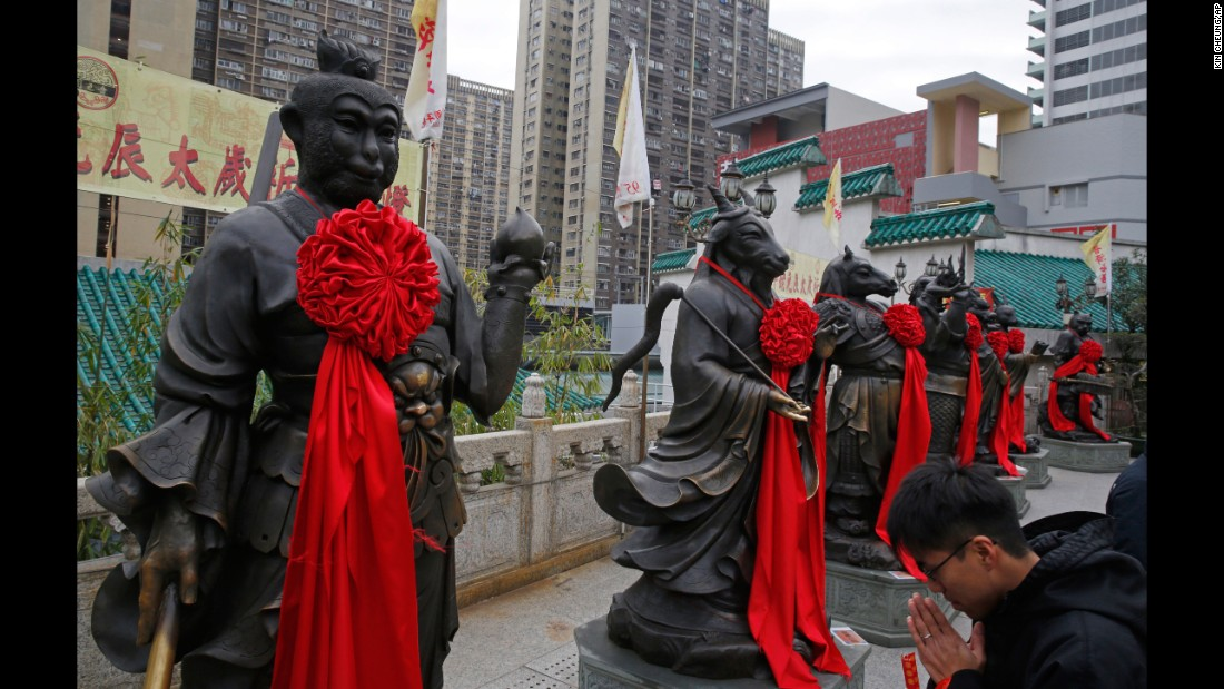 A visitor prays in front of a monkey statue at the Wong Tai Sin Temple in Hong Kong on Wednesday, February 3.