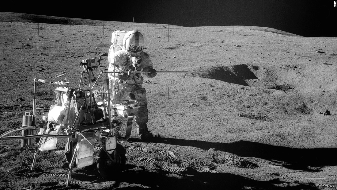 Shepard stands beside a portable workbench set up on the moon.