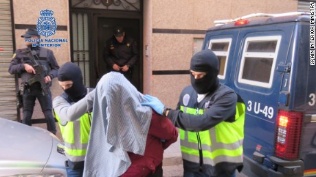 Spanish police wearing balaclavas escort one of the terror suspects arrested Sunday.