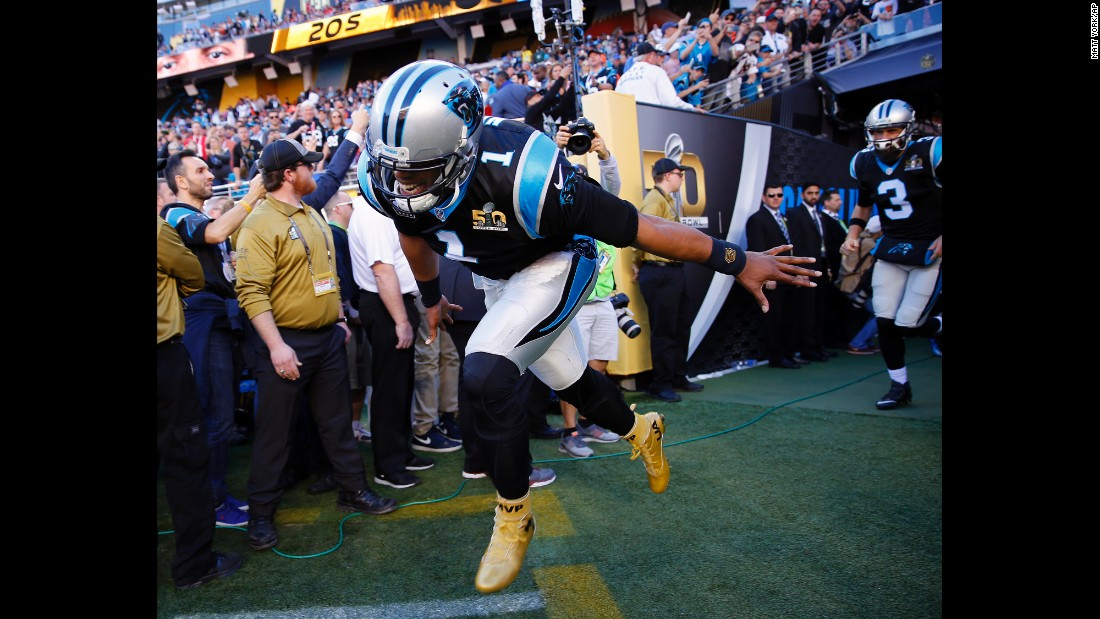 Newton and the Panthers run onto the field before the game.