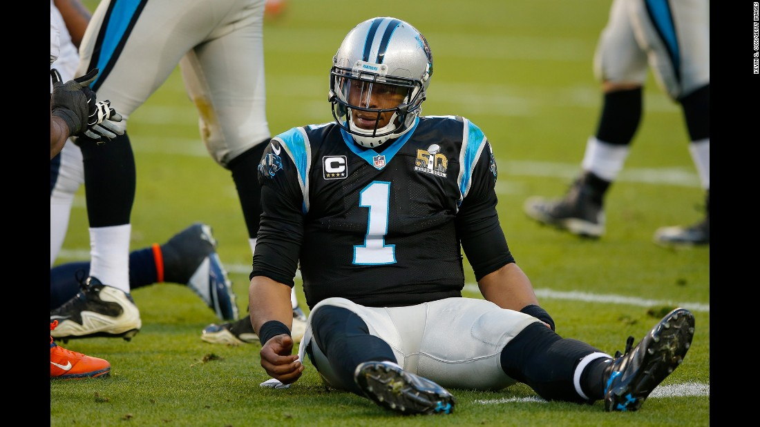 Newton sits on the turf after being hit in the first half. At halftime, Carolina trailed Denver 13-7.