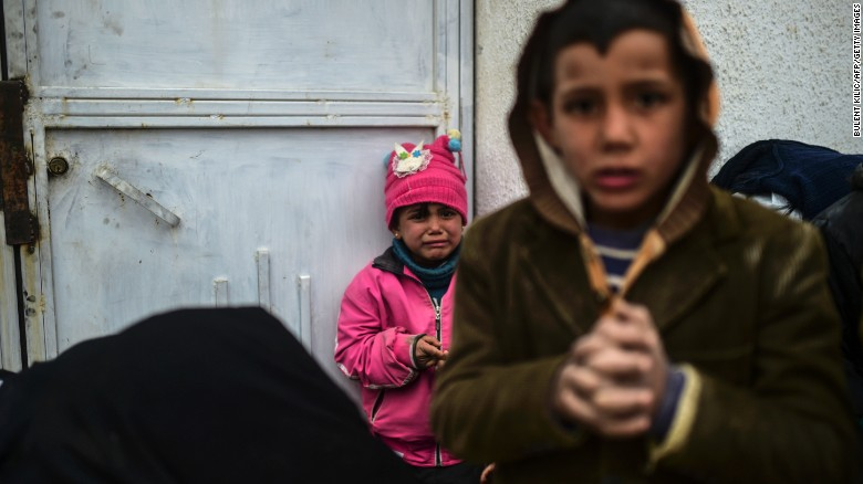 A refugee girl reacts near the Turkish border crossing gate as Syrians fleeing the northern embattled city of Aleppo wait on February 6, 2016 in Bab al-Salama, near the city of Azaz, northern Syria. Thousands of Syrians were braving cold and rain at the Turkish border Saturday after fleeing a Russian-backed regime offensive on Aleppo that threatens a fresh humanitarian disaster in the country's second city. Around 40,000 civilians have fled their homes over the regime offensive, according to the Syrian Observatory for Human Rights monitor. / AFP / BULENT KILIC        (Photo credit should read BULENT KILIC/AFP/Getty Images)