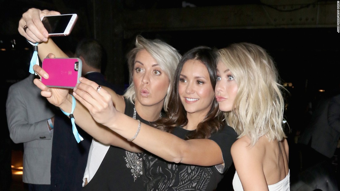 Actress Nina Dobrev, center, takes selfies with hairstylist Riawna Capri, left, and actress Julianne Hough at a party in San Francisco on Saturday, February 6.