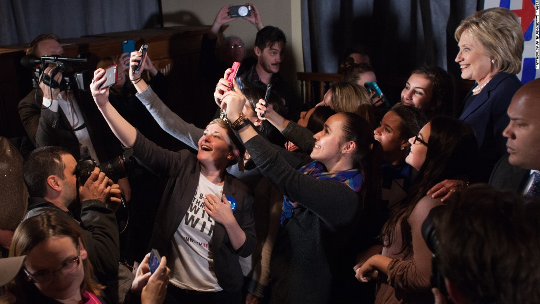People take selfies with Democratic presidential candidate Hillary Clinton, far right, at a debate-watching party in Durham, New Hampshire, on Thursday, February 4.
