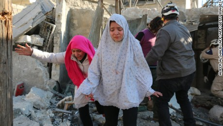 Syrian girls react following a reported Syrian regime air strike in a rebel-controlled area in the northern city of Aleppo in February.