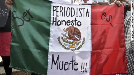 "A woman holds Mexican flag with an inscription that reads ""To Be a Honest Journalist is Death"" during a demonstration for the murder of photojournalist Ruben Espinosa, at Angel of  Independence square in Mexico City, on August 2, 2015. Espinosa was found shot dead on August 1, 2015, in Mexico City, where he had moved two months ago from Veracruz, after reporting strong threats from the government of the state. Since 2010, 11 journalists have been killed and four others have gone missing in Veracruz. AFP PHOTO/ Yuri CORTEZ        (Photo credit should read YURI CORTEZ/AFP/Getty Images)"