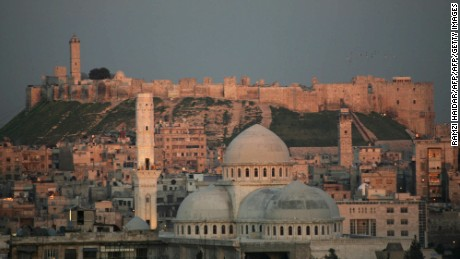 "A picture taken 17 March 2006 shows a general view of the historic Syrian city of Aleppo, 350 kms north of Damascus, with its landmark cytadel in the background. Hundreds of Arab and foreign personalities will gather in Aleppo this weekend to celebrate its choice as the Arab world's capital of Islamic culture for 2006. Syrian Culture Minister Riad Nassan Agha said yesterday Aleppo was chosen by the Organization of the Islamic Conference (OIC) because of its role as the ""main point of passage between East and West."" Two days of inaugural festivities will kick off 18 March 2006 with the rededication of the 12th-century Great Mosque (C), which has been under restoration for the past five years. AFP PHOTO/RAMZI HAUDAR (Photo credit should read RAMZI HAIDAR/AFP/Getty Images)"