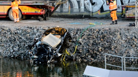 A damaged car is pulled from a canal in Sodertalje, Sweden, on Saturday.