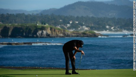 Phil Mickelson bows his head after seeing his birdie putt on 18 drift past the final hole.