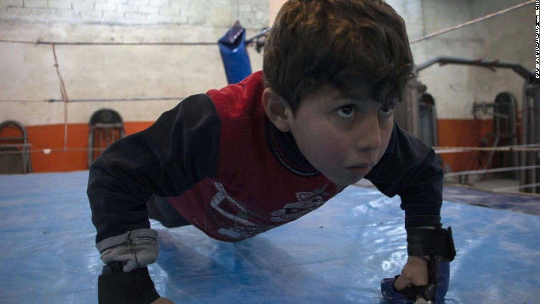 A young Syrian boy practices push-ups during a training session at the Shahba boxing club in Aleppo on February 10, 2016.