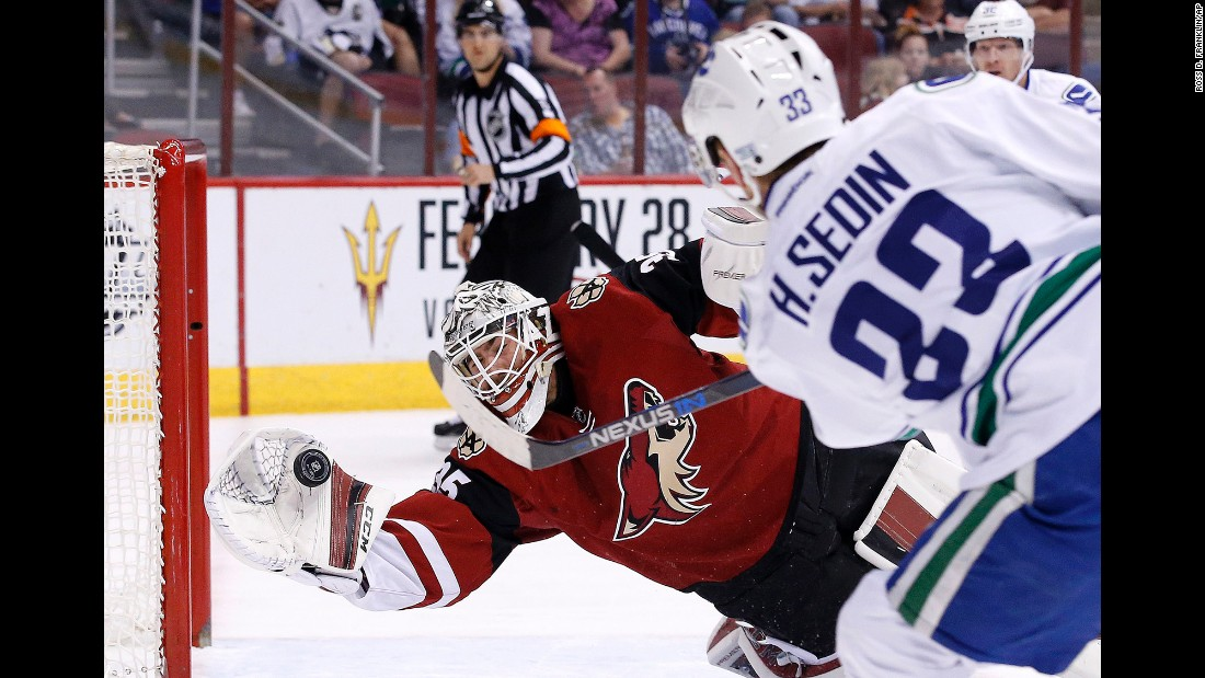 Arizona goalie Louis Domingue makes a diving save on Vancouver's Henrik Sedin during an NHL hockey game in Glendale, Arizona, on Wednesday, February 10.