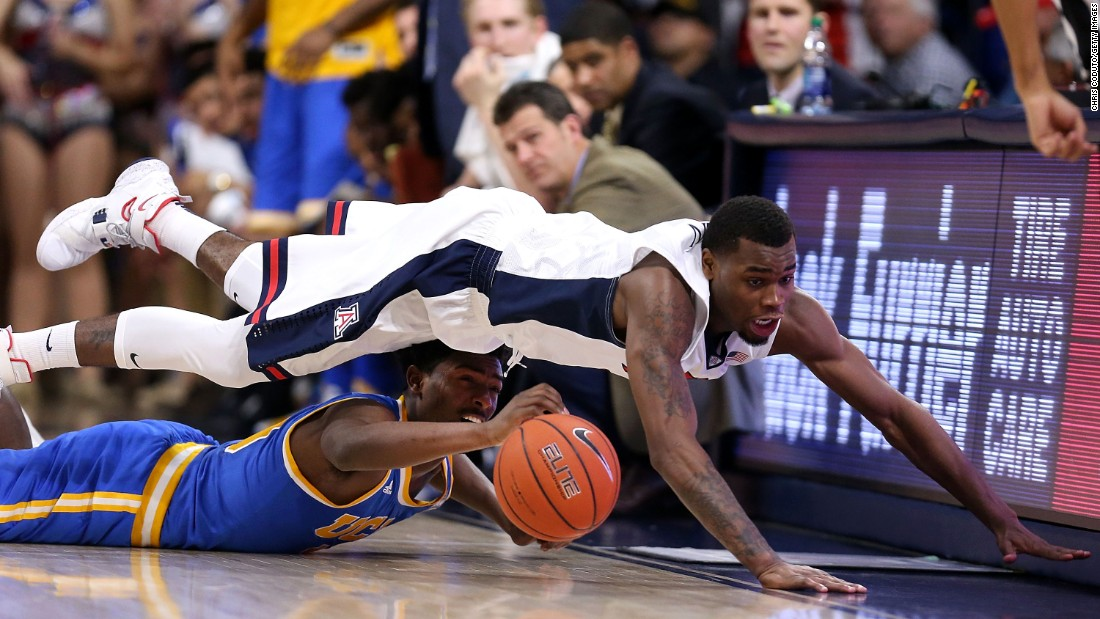 Arizona's Kadeem Allen dives over UCLA's Isaac Hamilton during a Pac-12 game in Tucson, Arizona, on Friday, February 12.