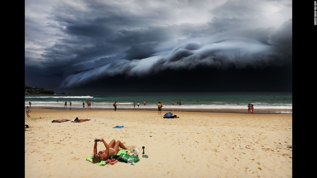 A massive cloud looms over Sydney's Bondi Beach as a sunbather reads on November 6.