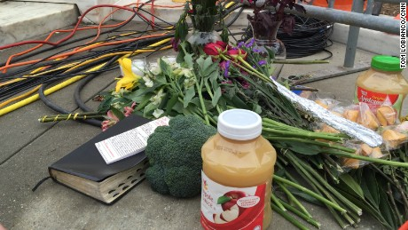"Outside the Supreme Court on February 19, 2016, mourners leave flowers and jars of applesauce — a nod to an Justice Antonin Scalia's dissent in which he wrote that the majority's opinion was ""pure applesauce."""
