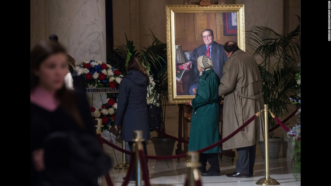 People look at a portrait of Scalia while paying their respects in Washington on February 19.