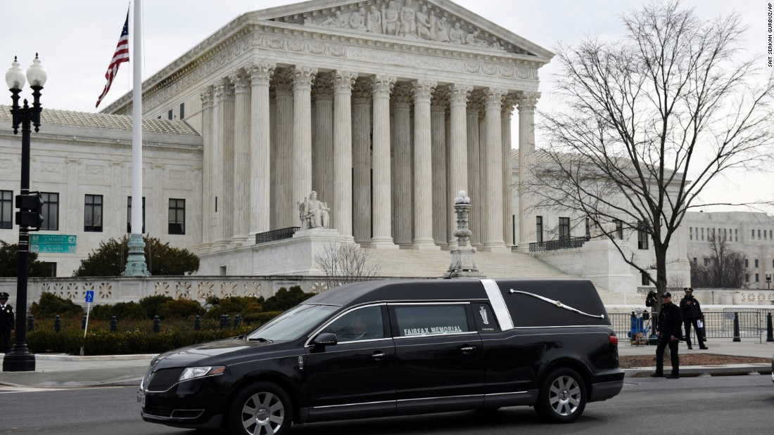 A hearse carrying the casket departs the U.S. Supreme Court Building on February 20.