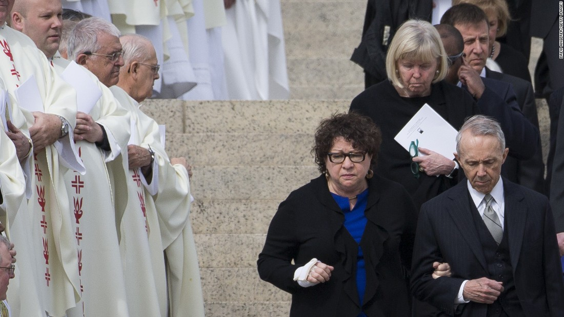 Supreme Court Justice Sonia Sotomayor, center, and former Justice David Souter, right, walk down the steps of the Basilica of the National Shrine of the Immaculate Conception at the end of the funeral.